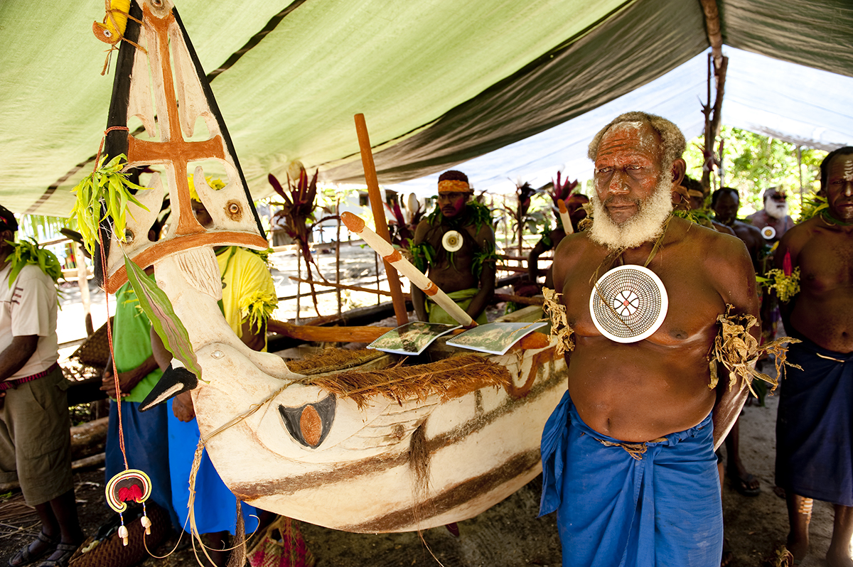 Joseph Baras, a Masahet elder proudly stands beside the Kabelbel canoe on the day of the launch of the Lihir Cultural Heritage Plan and the Kabelbel canoe.