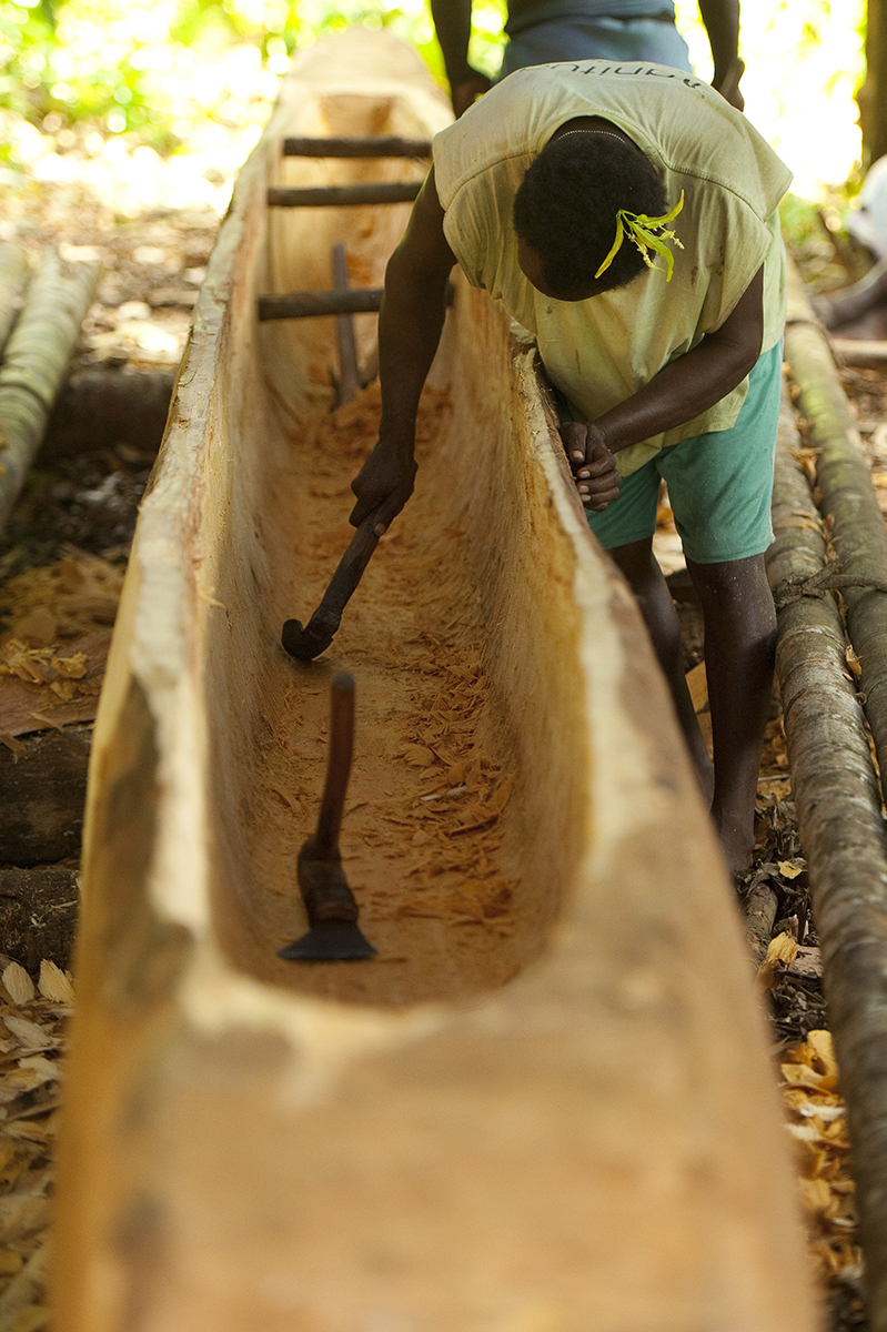 Isidore Lumnga removing more chips from the bottom of the canoe.